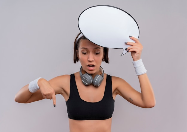 Young fitness woman in sportswear with headband holding blank speech bubble sign pointing wi finger down looking surprised standing over white wall