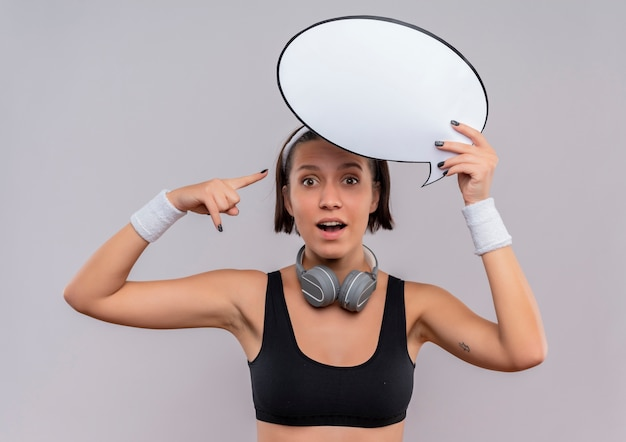 Young fitness woman in sportswear with headband holding blank speech bubble sign pointing with finger to it looking surprised standing over white wall