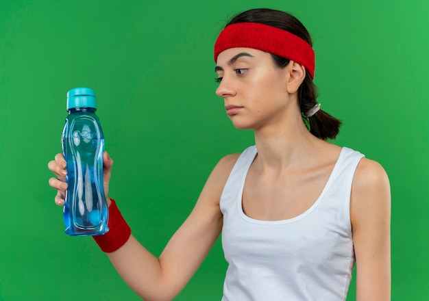 Young fitness woman in sportswear with headband holding bottle of water looking at it displeased with skeptic expression standing over green wall