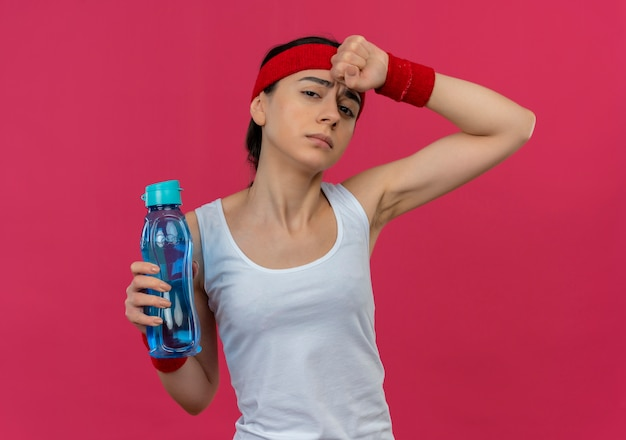Young fitness woman in sportswear with headband holding bottle of water looking tired and exhausted standing over pink wall