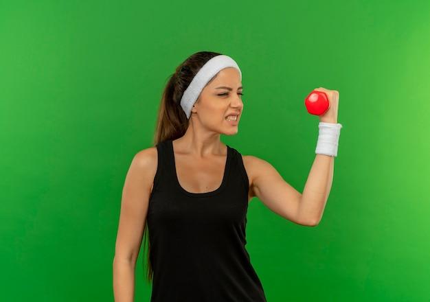 Giovane donna fitness in abiti sportivi con fascia tenendo il manubrio facendo esercizi cercando tesa in piedi sopra la parete verde