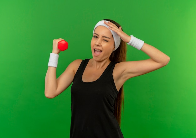 Young fitness woman in sportswear with headband holding dumbbell doing exercises smiling and winking standing over green wall