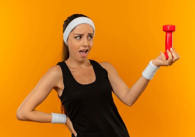 Giovane donna fitness in abiti sportivi con fascia tenendo il manubrio guardando confuso in piedi sopra la parete arancione