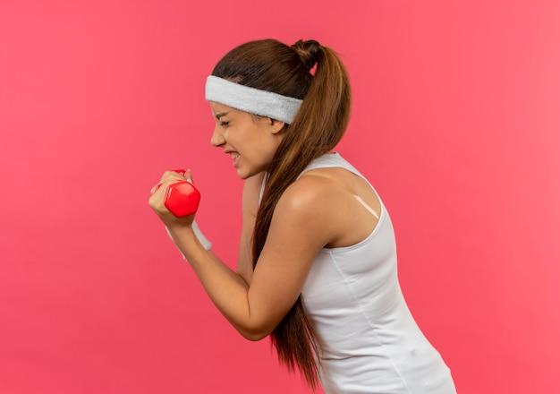 Giovane donna fitness in abiti sportivi con fascia tenendo il manubrio cercando tesa facendo esercizi in piedi sopra la parete rosa