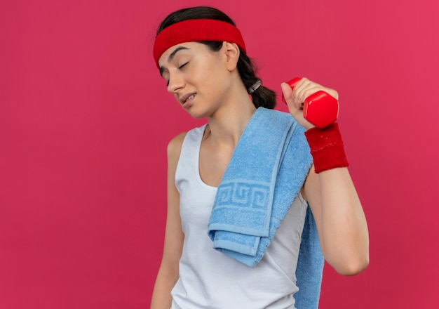 Giovane donna fitness in abiti sportivi con fascia tenendo il manubrio in mano alzata facendo esercizi che sembrano stanchi e annoiati in piedi sopra il muro rosa