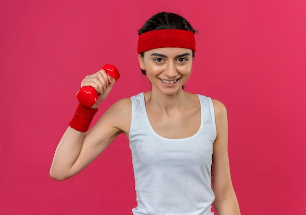 Young fitness woman in sportswear with headband holding dumbbell in raised hand smiling confident doing exercises standing over pink wall