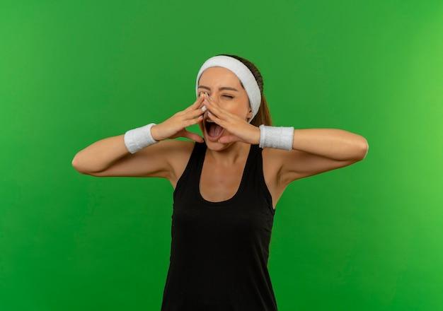 Giovane donna di forma fisica in abiti sportivi con la fascia che tiene le mani vicino alla bocca che grida eccitato in piedi sopra la parete verde