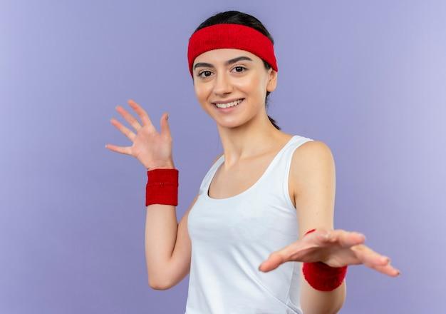 Giovane donna fitness in abiti sportivi con fascia tendendo le palme facendo gesto di difesa sorridente in piedi sopra la parete viola