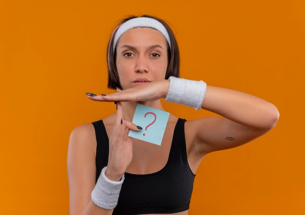Young fitness woman in sportswear with headband holding reminder paper with question mark making time out gesture with hands with serious face standing over orange wall