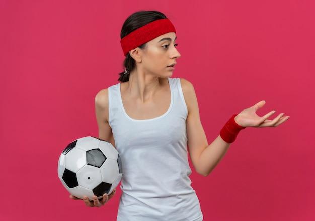 Giovane donna fitness in abbigliamento sportivo con fascia tenendo il pallone da calcio guardando da parte con il braccio fuori in piedi sopra la parete rosa