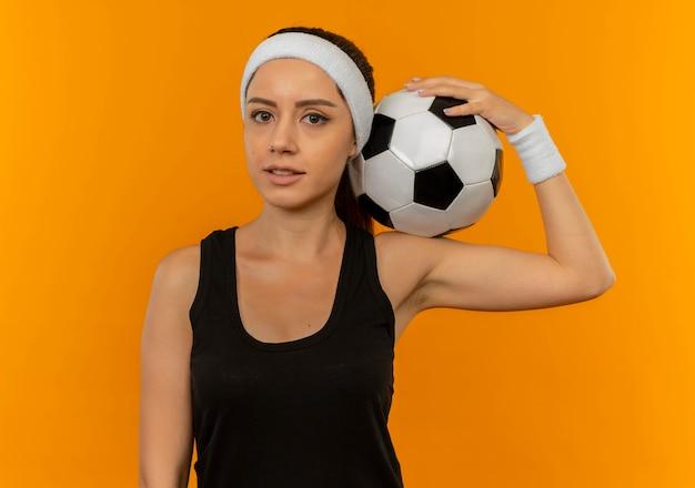 Giovane donna fitness in abbigliamento sportivo con fascia tenendo il pallone da calcio guardando fiducioso in piedi sopra la parete arancione