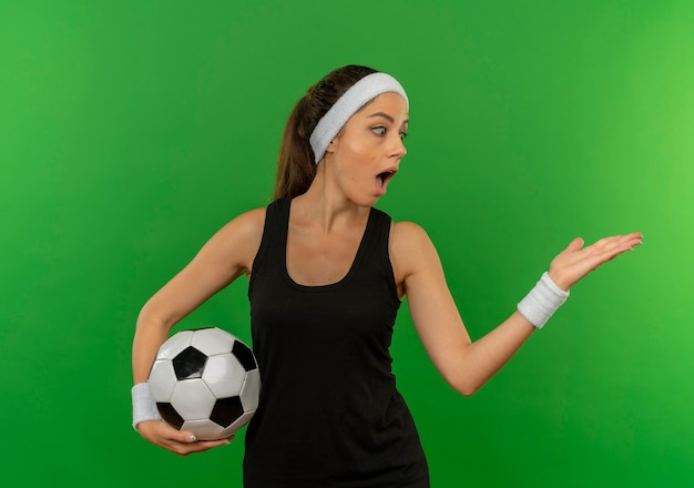 Giovane donna di forma fisica in abbigliamento sportivo con la fascia che tiene il pallone da calcio che indica con il braccio della sua mano al lato che sembra sorpreso in piedi sopra la parete verde