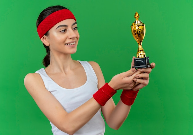 Young fitness woman in sportswear with headband holding trophy looking at it smiling confident standing over green wall