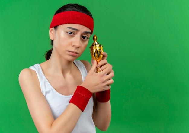 Giovane donna fitness in abiti sportivi con fascia tenendo il trofeo con espressione triste sul viso in piedi sopra la parete verde