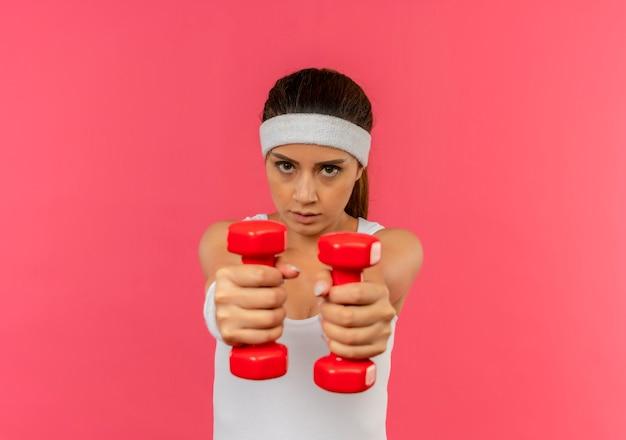 Giovane donna fitness in abiti sportivi con archetto che tiene due manubri facendo esercizi guardando fiducioso in piedi sopra il muro rosa