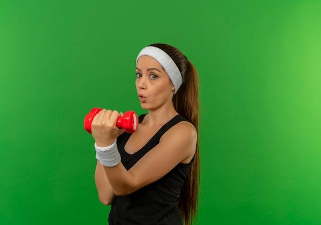 Giovane donna di forma fisica in abiti sportivi con la fascia che tiene due manubri facendo esercizi che sembrano confusi e sorpresi in piedi sopra la parete verde
