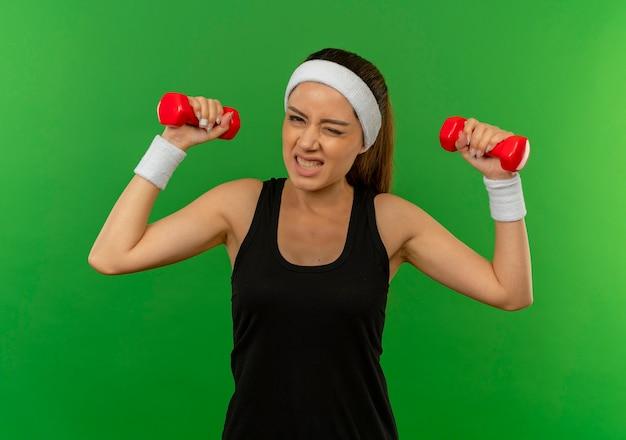 Giovane donna di forma fisica in abiti sportivi con fascia che tiene due manubri facendo esercizi con espressione infastidita in piedi sopra la parete verde