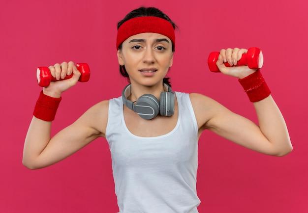Giovane donna di forma fisica in abiti sportivi con fascia che tiene due manubri facendo esercizi con espressione confusa in piedi sopra il muro rosa