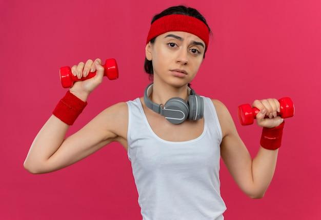 Giovane donna fitness in abiti sportivi con fascia tenendo due manubri facendo esercizi con espressione triste sul viso in piedi sopra la parete rosa