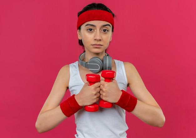 Giovane donna di forma fisica in abiti sportivi con fascia che tiene due manubri facendo esercizi con la faccia seria in piedi sopra il muro rosa