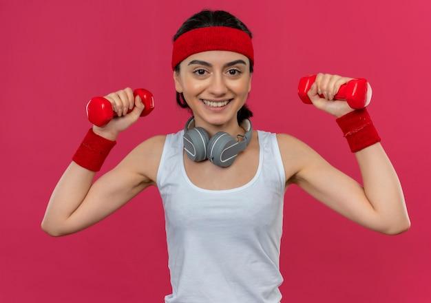 Giovane donna fitness in abiti sportivi con fascia che tiene due manubri facendo esercizi con il sorriso sul viso in piedi sopra la parete rosa
