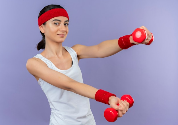 Giovane donna fitness in abiti sportivi con archetto che tiene due manubri nelle mani