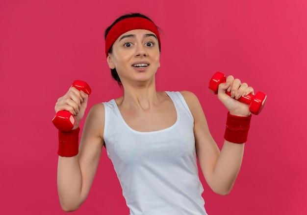 Giovane donna fitness in abiti sportivi con fascia tenendo due manubri in mani alzate facendo esercizi
