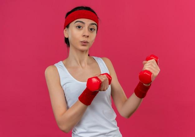 Giovane donna fitness in abiti sportivi con fascia tenendo due manubri in mani alzate guardando fiducioso facendo esercizi in piedi sopra il muro rosa