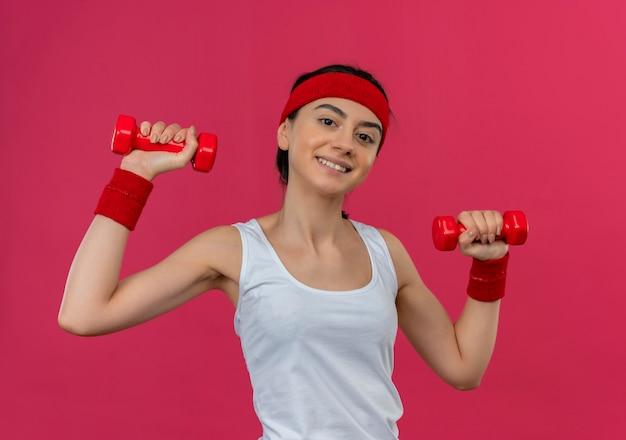 Giovane donna fitness in abiti sportivi con fascia tenendo due manubri in mani alzate sorridendo fiducioso facendo esercizi in piedi sopra il muro rosa