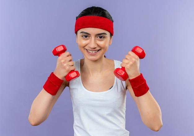 Giovane donna di forma fisica in abiti sportivi con fascia tenendo due manubri in mani alzate