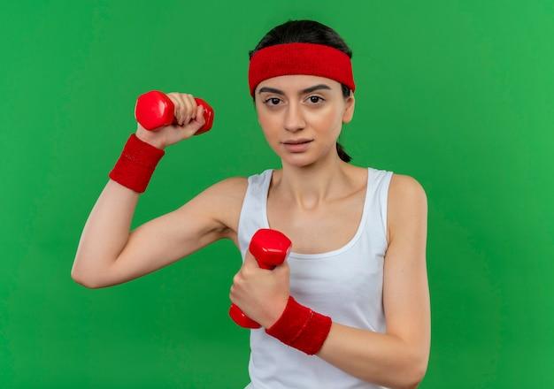 Giovane donna di forma fisica in abiti sportivi con fascia che tiene due manubri alzando le mani facendo esercizi fiduciosi con faccia seria in piedi sopra la parete verde