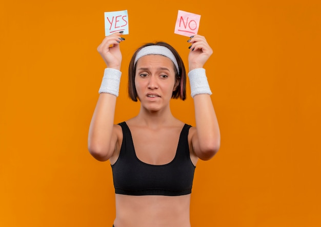 Young fitness woman in sportswear with headband holding two reminder papers with word yes and no in raised hands looking confused standing over orange wall