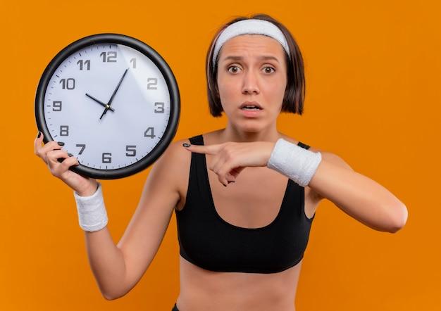 Giovane donna fitness in abbigliamento sportivo con fascia tenendo l'orologio da parete che punta con il dito indice ad esso guardando confuso e molto ansioso in piedi sopra la parete arancione