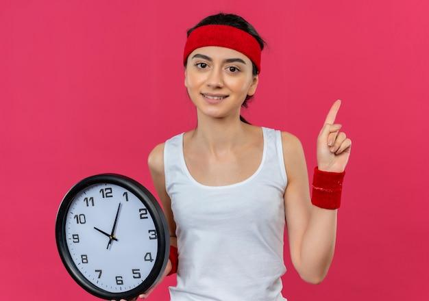 Giovane donna fitness in abbigliamento sportivo con fascia tenendo l'orologio da parete che mostra il dito indice guardando fiducioso in piedi sopra la parete rosa