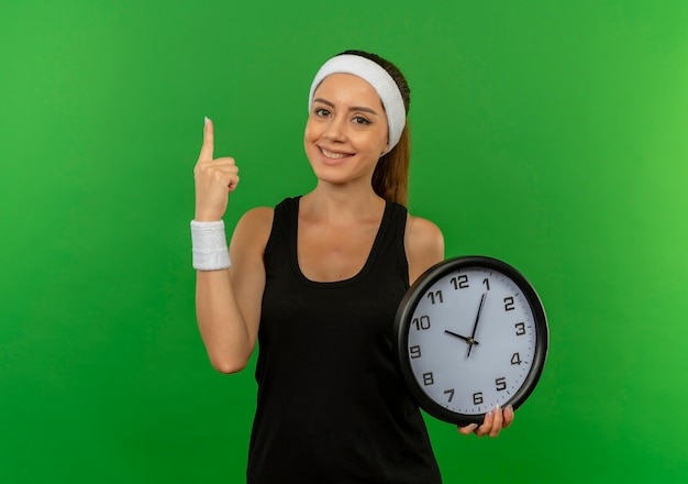 Young fitness woman in sportswear with headband holding wall clock showing index finger smiling confident standing over green wall