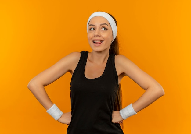 Young fitness woman in sportswear with headband looking aside happy and positive smiling standing over orange wall