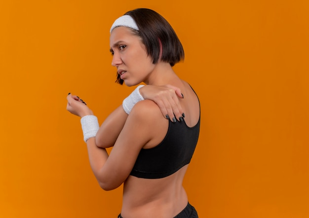 Young fitness woman in sportswear with headband looking unwell touching her shoulder feeling pain standing over orange wall