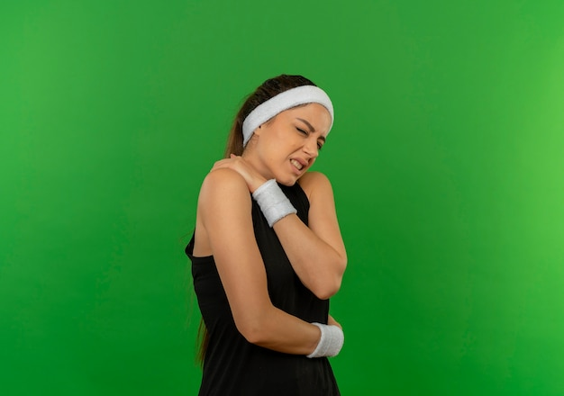 Giovane donna di forma fisica in abiti sportivi con la fascia cercando di stare male toccando la sua spalla avendo dolore in piedi sopra la parete verde