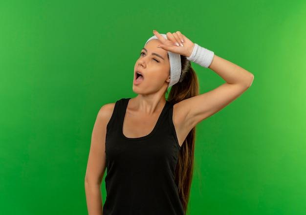 Giovane donna di forma fisica in abbigliamento sportivo con la fascia che osserva in su ammiccante che indica con il dito in su avendo nuova idea che sta sopra la parete verde