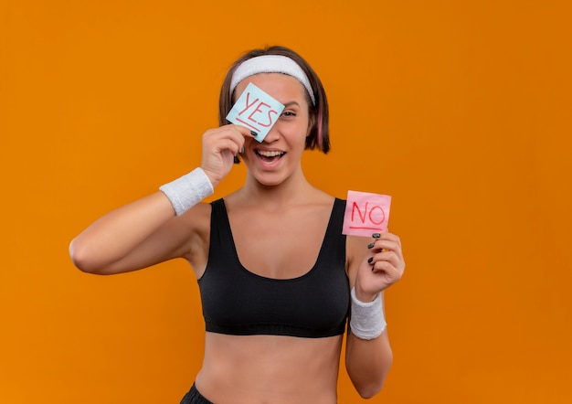 Young fitness woman in sportswear with headband showing two reminder papers with word yes and no smiling cheerfully covering with paper one eye standing over orange wall