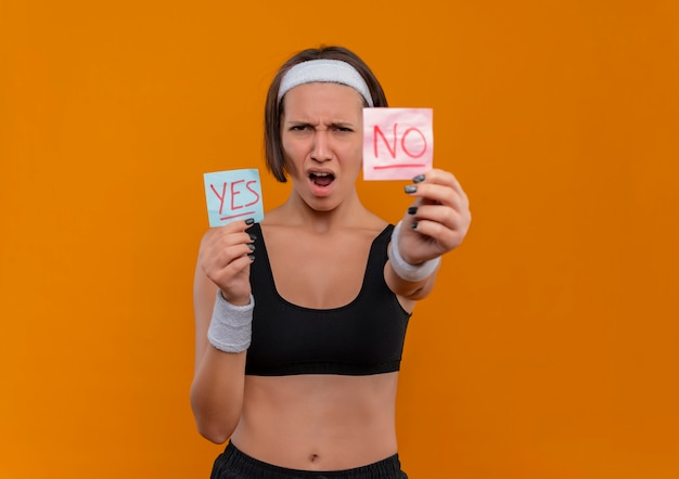 Young fitness woman in sportswear with headband showing two reminder papers with word yes and no smiling cheerfully standing over orange wall