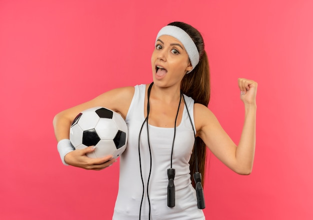 Young fitness woman in sportswear with headband and skipping rope around her neck holding soccer ball looking surprised