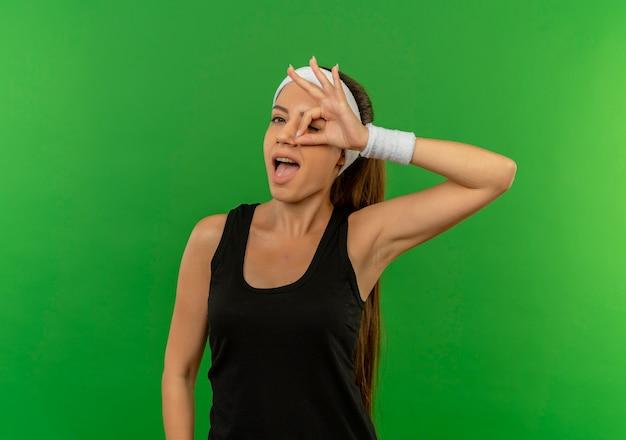 Giovane donna di forma fisica in abiti sportivi con la fascia che sorride allegramente facendo segno giusto guardando attraverso questo segno in piedi sopra la parete verde