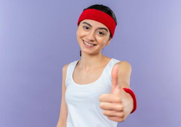 Giovane donna fitness in abiti sportivi con fascia sorridendo allegramente mostrando i pollici in su in piedi sul muro viola