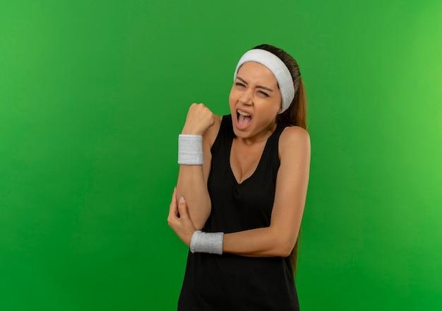 Giovane donna fitness in abiti sportivi con fascia toccando il gomito avendo dolore in piedi sopra la parete verde