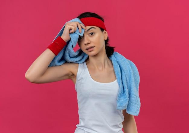 Giovane donna fitness in abiti sportivi con fascia e asciugamano intorno al collo stanco ed esausto in piedi sopra il muro rosa