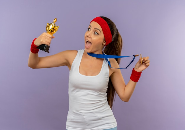 Young fitness woman in sportswear with headband with gold medal around her neck holding her trophy shouting happy and excited standing over grey wall
