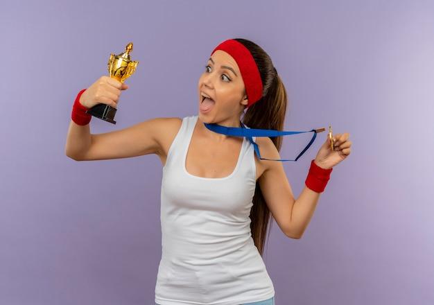 Giovane donna fitness in abbigliamento sportivo con fascia con medaglia d'oro al collo che tiene il suo trofeo gridando felice ed eccitato in piedi sopra il muro grigio