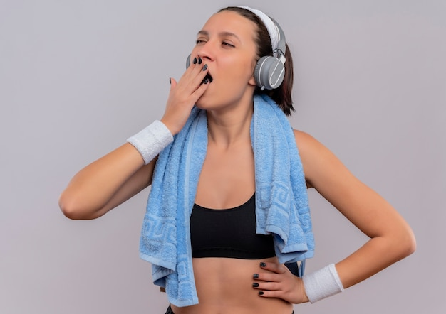 Young fitness woman in sportswear with headphones on head and towel on her neck tired wants to sleep yawning standing over white wall