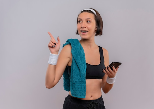 Young fitness woman in sportswear with towel on shoulder holding smartphone pointing with finger to the side smiling cheerfully standing over white wall